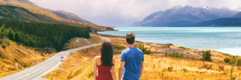 New Zealand travel people looking at Mount Cook Aoraki far in the landscape. Couple tourists walking at Peter's lookout, banner panorama copy space on background.